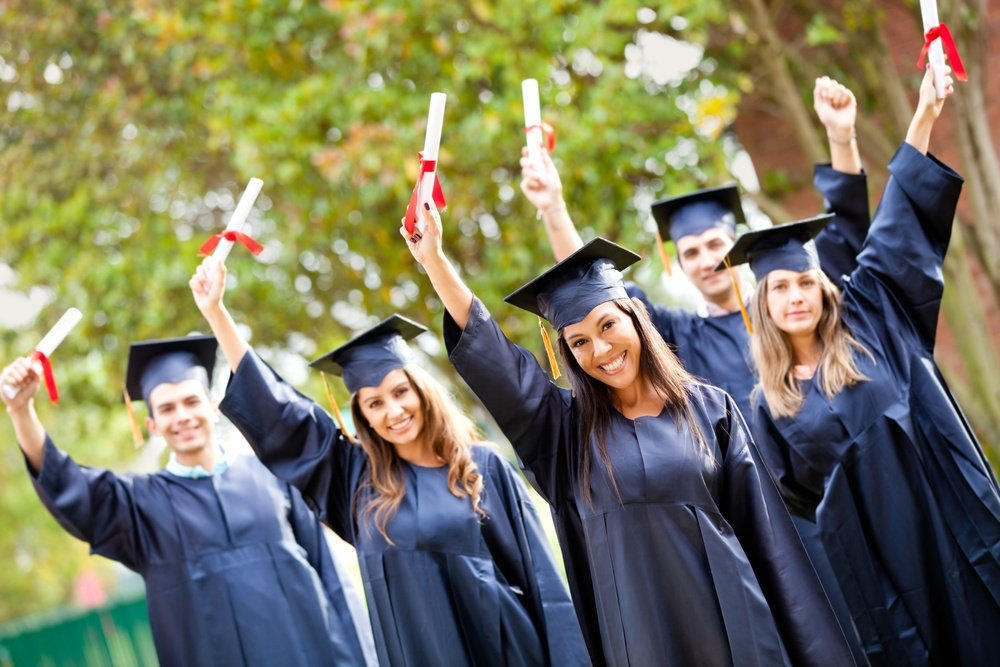 Happy group of students with arms up at their graduation