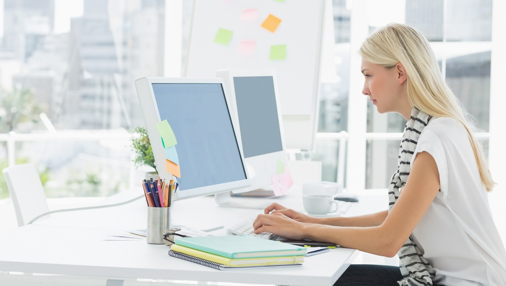 Side view of a casual young woman using computer in a bright office